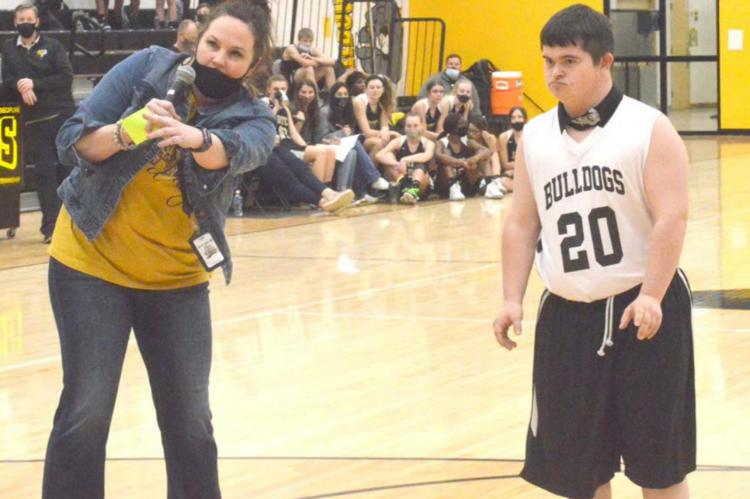 Bryce Lide prepares to shoot five shots in an attempt to raise money for the North Zulch basketball program Friday as part of their Shoot-athon fundraiser. (Also pictured: North Zulch Coach Melissa Padgett, who emceed the halftime event) CAMPBELL ATKINS